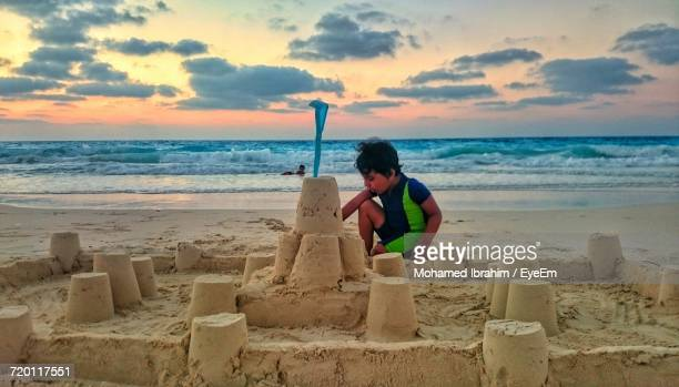 Boy Making Sandcastle At Beach Against Sky During Sunset