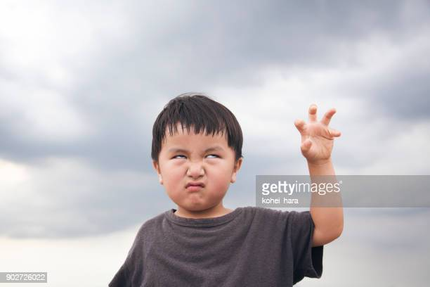 Boy making scary face under a cloudy sky