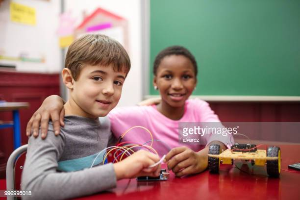 Boy making science project with girl in school