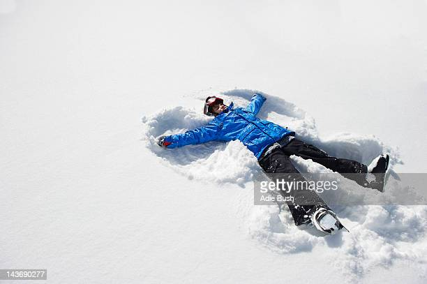 boy making snow angel - snow angel stock photos and pictures