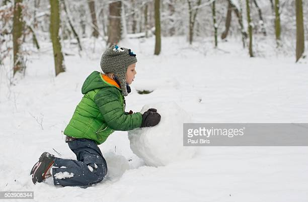 Boy making snowman outdoors
