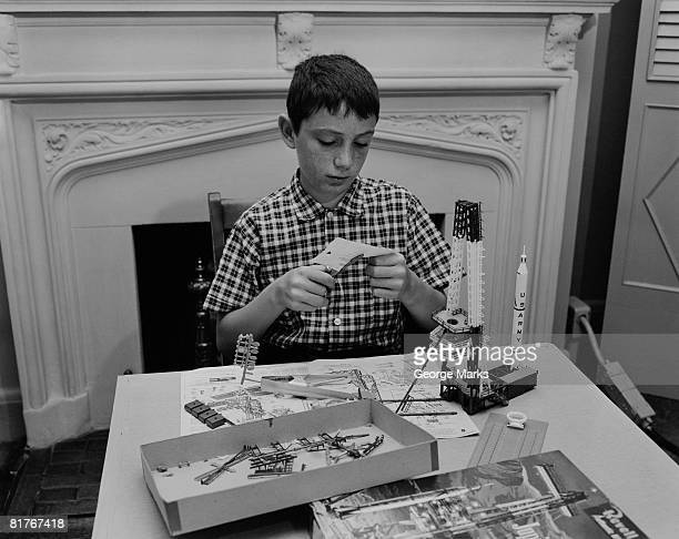 Boy (12-13) making space rocket model in living room