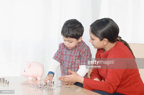 Boy making stacks of coins near a piggy bank with his mother sitting beside him