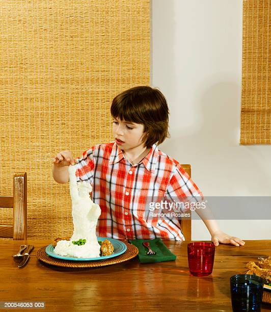 Boy (4-6) making statue out of mashed potatoes