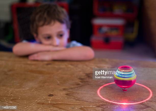 Boy marvels at his toy spinning