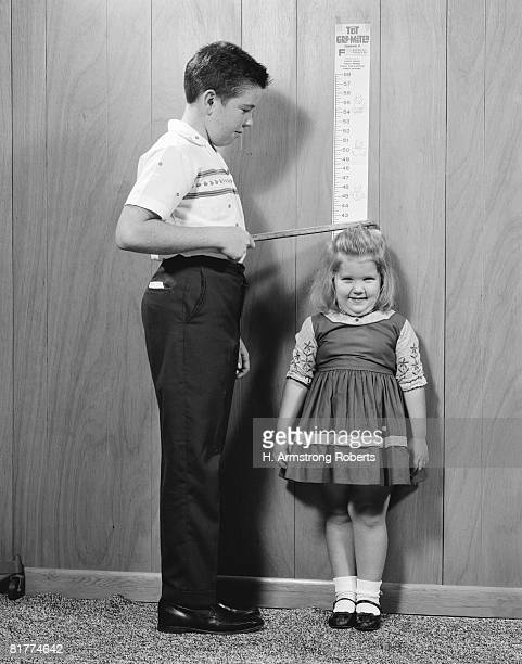 Boy measuring height of sister on wall gro-meter chart.