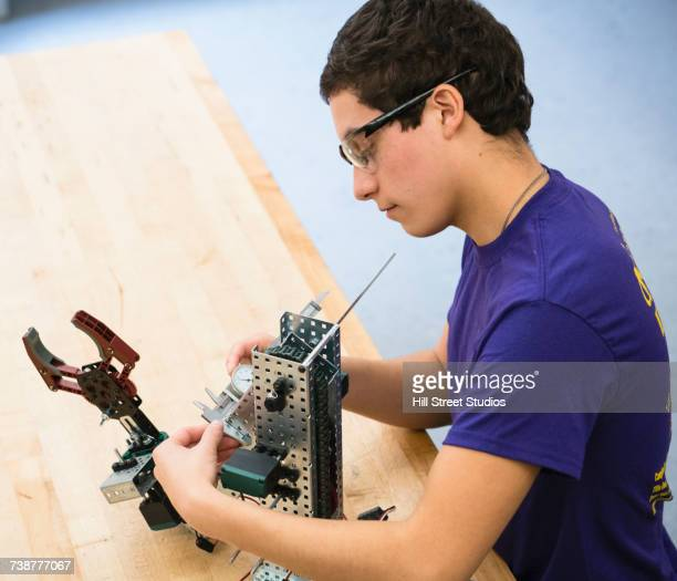 Boy measuring robotics with caliper at school