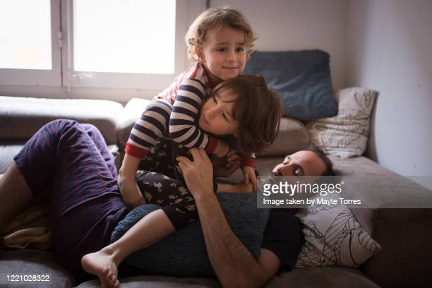 boy messing with dad and brother in the sofa - innocence stock pictures, royalty-free photos & images