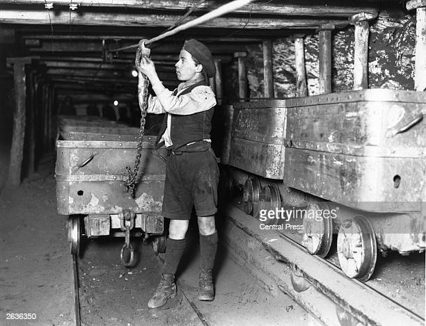 A boy miner underground at Ashington colliery fixes the ropes for the coal carts