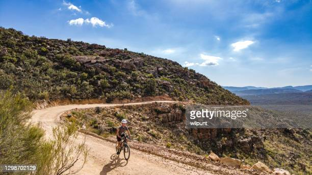 boy mountain biking cycling a dirt track mountain pass on a summers day - south africa stock pictures, royalty-free photos & images