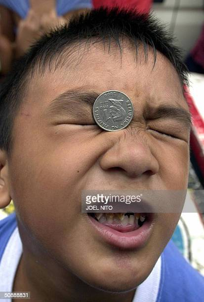 A boy moves a coin across his face entirely with facial expressions as part of a party game held during a village festival in a suburb of the...