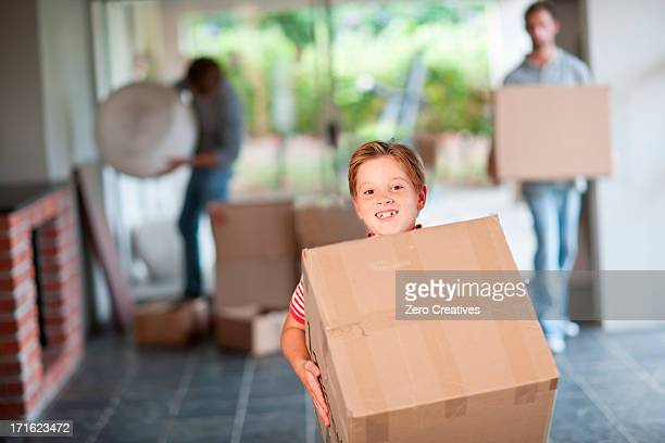Boy moving house carrying cardboard box