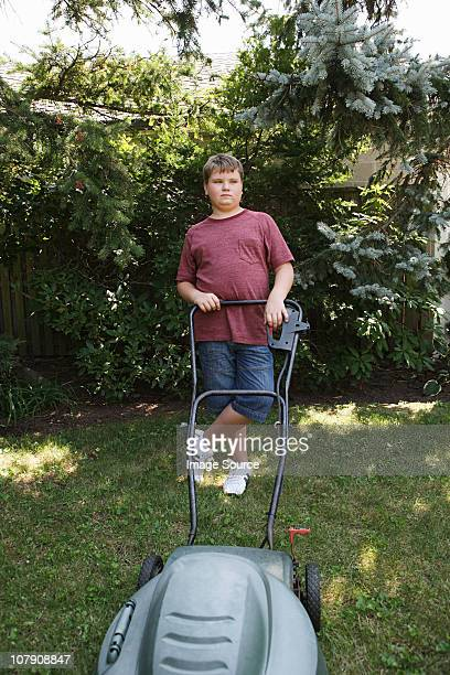 boy mowing grass with lawnmower - chubby boy stock photos and pictures