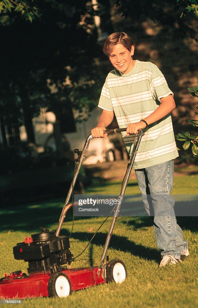 Boy mowing lawn : Stockfoto