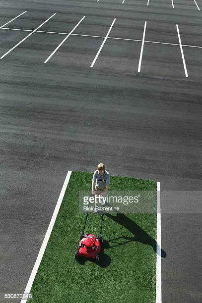Boy mowing patch of artificial lawn in parking lot