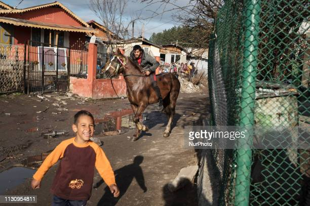 Boy named Fidan runs out of the way as a man rides his horse quickly down a street in the Fakulteta neighborhood of Sofia, March 16, 2019 during...