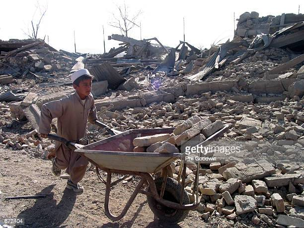 A boy named Mohammad Naim hauls away bricks November 20 2001 from a building that was destroyed by a bomb dropped by US war planes in Kabul...