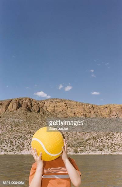 Boy near Lake Holding Ball