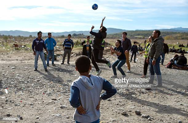 A boy observes as fellow migrants and refugees play volleyball while waiting to enter a registration camp after crossing the GreekMacedonian border...