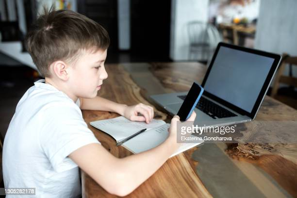 a boy of 10-11 years old in a white t-shirt sits at home at a laptop and studies online on the computer. homeschooling. white screen. - 10 11 years stock pictures, royalty-free photos & images