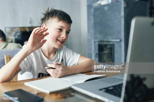 a boy of 10-11 years old in a white t-shirt sits at home at a laptop and communicates with friends on a laptop. - 10 11 years stock pictures, royalty-free photos & images