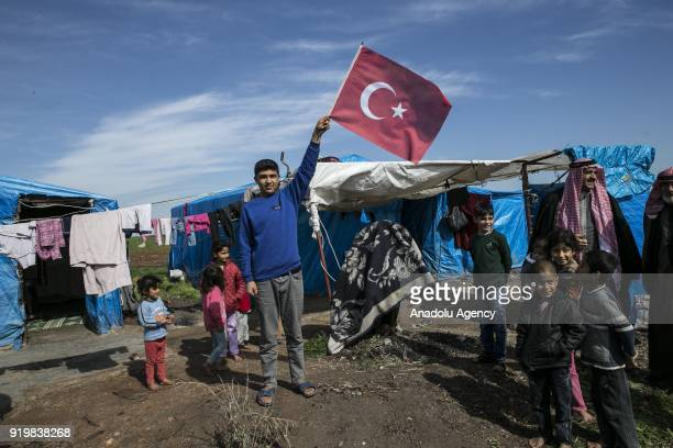A boy of a family fled from Jinderes district in Syria and sheltered in Reyhanli waves a Turkish flag in Hatay Turkey on February 18 2018 Total of 8...