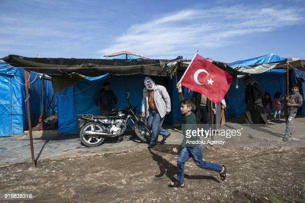 A boy of a family fled from Jinderes district in Syria and sheltered in Reyhanli waves a Turkish flag while running in Hatay Turkey on February 18...