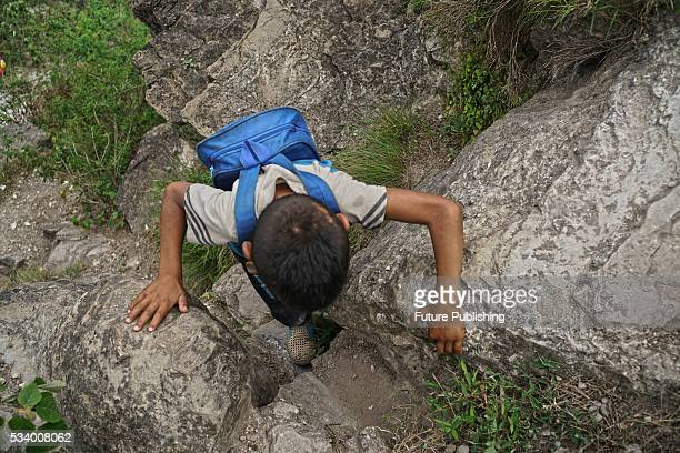A boy of Atule'er Village climbs rock on his way home in Zhaojue county in southwest China's Sichuan province on May 14 2016 in Zhaojue China There...