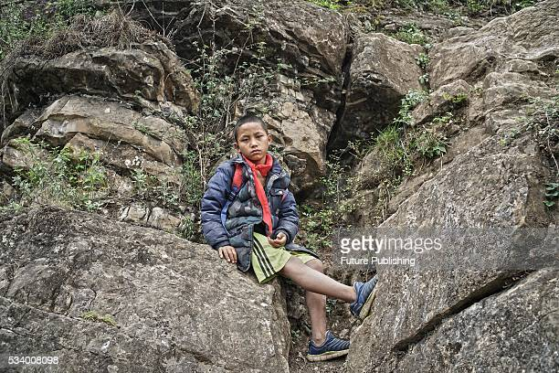 A boy of Atule'er Village takes a rest during climbing the a cliff on his way home in Zhaojue county in southwest China's Sichuan province on May 14...
