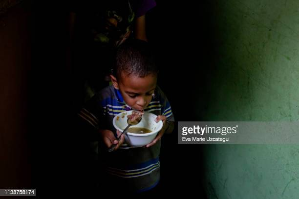 Boy of Barrio Unión Sector Las Casitas eat soup prepared and donated by Alto Restaurant in the house of a neighbor at Petare on April 12, 2019 in...