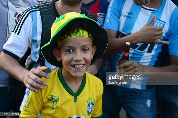 A boy of Brazil poses with fans of Argentina prior a match between Argentina and Brazil as part of FIFA 2018 World Cup Qualifiers at Mineirao Stadium...
