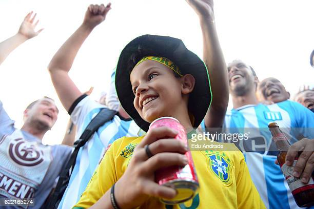 A boy of Brazil smiles while fans of Argentina cheer for their team prior a match between Argentina and Brazil as part of FIFA 2018 World Cup...