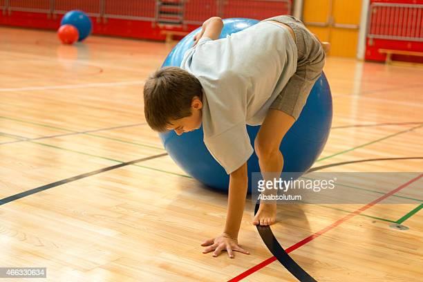 Der Elf Junge spielt mit blauen Fitness-Ball, Sporthalle
