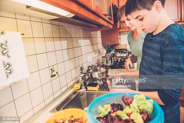 Boy of Twelve and Mother Cleaning Salad, Home Kitchen, Europe