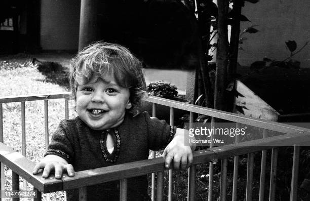 boy of two in his playpen, smiling at camera - filmato d'archivio foto e immagini stock