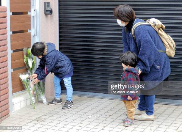 A boy offers a flower bouquet at home of late comedian Ken Shimura on March 30 2020 in Mitaka Tokyo Japan Popular comedian Shimura died of the novel...
