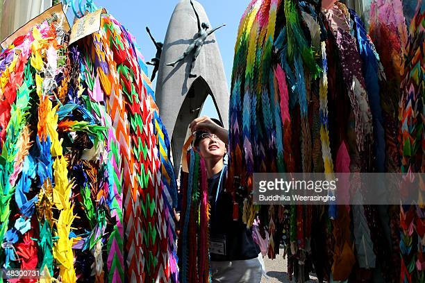 A boy offers colorful paper cranes at the Children's Peace Monument to honor the victims of the 1945 Atomic bomb at the Hiroshima Peace Memorial Park...
