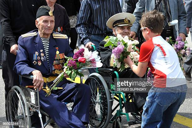 A boy offers flowers to World War II veterans in the central Ukrainian city of Sevastopol the main base of the Russian Black Sea Fleet during a...