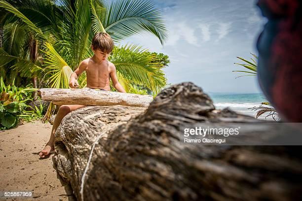 Boy on a beach sitting on a log