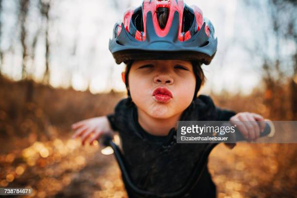 boy on a bicycle wearing a helmet puckering lips - cycling helmet stock photos and pictures