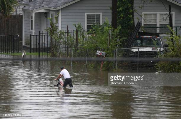 A boy on a bike rides in the flooded waters on Hopper Rd on September 19 2019 in Houston Texas Gov Greg Abbott has declared much of Southeast Texas...