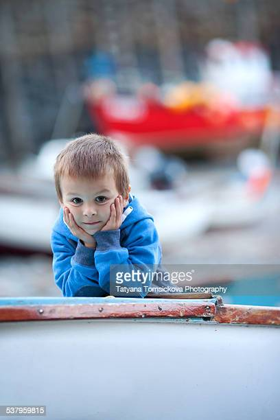 Boy on a boat, evening time, looking at camera