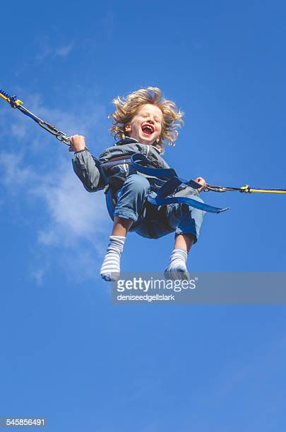 Boy on a bungee swing laughing