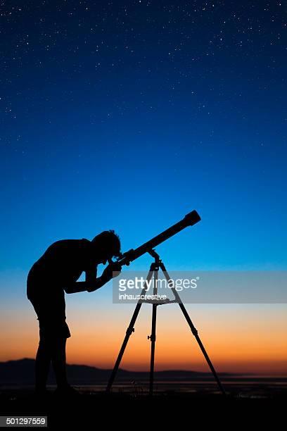 Boy on a clear night looking thru a telescope