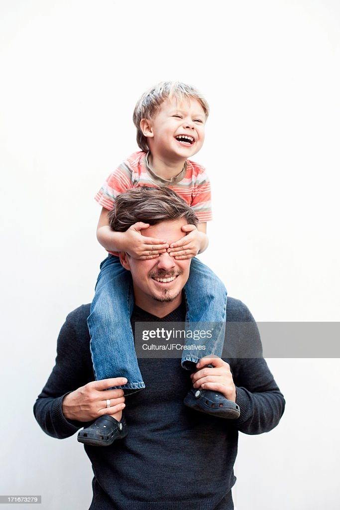 Boy on a father's shoulders, covering his eyes : Stock Photo
