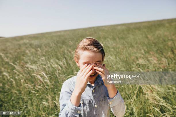 Boy on a field rubbing his eyes