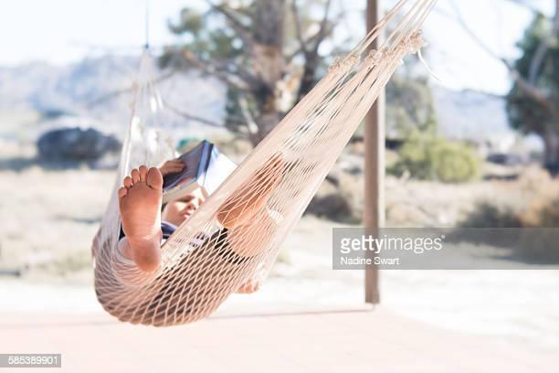 Boy on a hammock reading a book