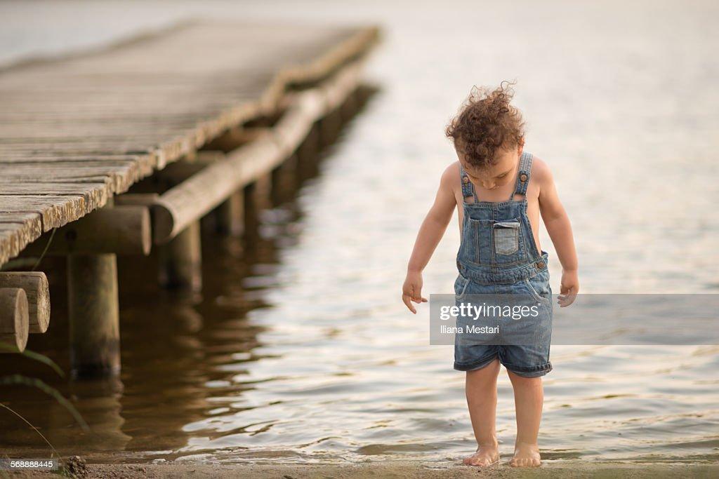 Boy on a lake's beach : Stock Photo
