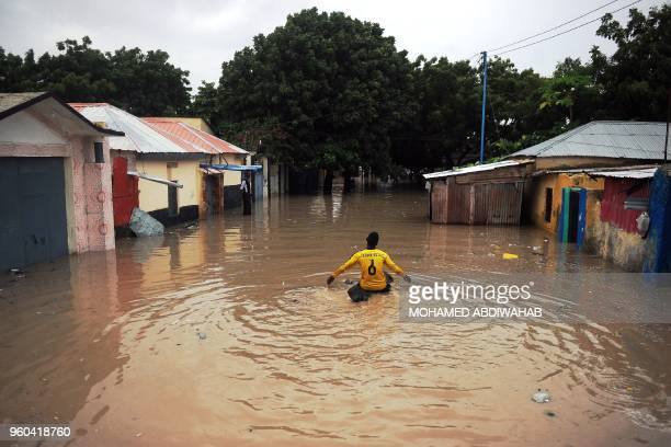 TOPSHOT A boy on a log floats down a flooded street at Wadajir district of Mogadishu on May 20 2018 after homes were inundated in Somalia's capital...