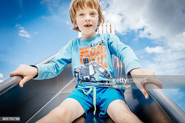 boy on a slide - graphic t shirt stock pictures, royalty-free photos & images